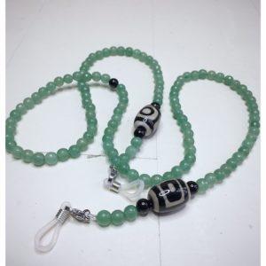 Łańcuszek do okularów z kamieni w kolorze zielonym z czarno białym dodatkiem na lnianej torebce opakunkowej.