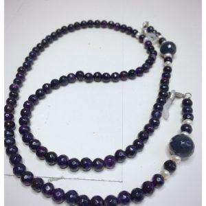 Łańcuszek do okularów z kamieni w kolorze ciemno fioletowym z białymi dodatkami na lnianej torebce opakunkowej.