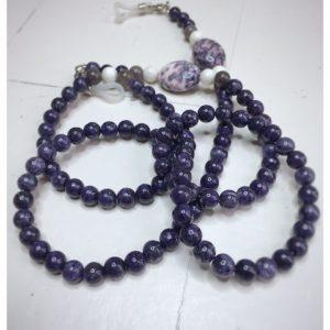 Łańcuszek do okularów z kamieni w fioletowo, szarym i kremowym na lnianej torebce opakunkowej.