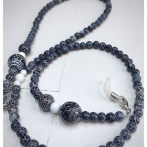 Łańcuszek do okularów z kamieni w kolorze czarno białym na lnianej torebce opakunkowej.