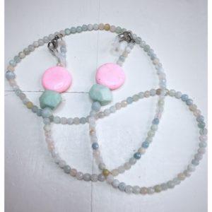 Łańcuszek do okularów z kamieni w kolorach pastelowych seledynowo różowych na lnianej torebce opakunkowej.