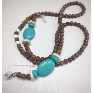 Łańcuszek do okularów z kamieni w kolorze szaro brązowym z beżowymi dodatkami na lnianej torebce opakunkowej.