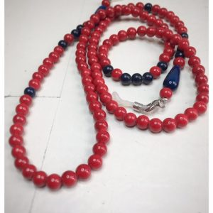 A chain for glasses made of red stones with navy blue accessories on a linen bag.