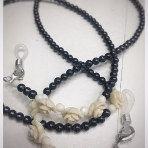 A chain for glasses made of black stones with cream roses and pebbles between them.