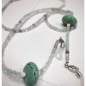 A chain for glasses made of celadon-violet glass stones with a celadon larger stone on a linen packaging bag.