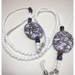 Łańcuszek do okularów z kamieni koloru białego i większymi biało-szaro-fioletowymi na lnianej torebce opakunkowej.