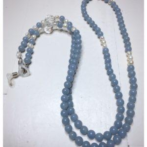 Łańcuszek do okularów dobro to obrazek jasnoniebieskiego łańcuszka z kamieni naturalnych z perłami i przezroczystymi kryształami.